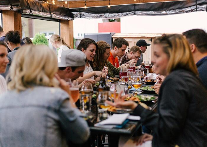 Pessoas alegres almoçando em restaurante lotado