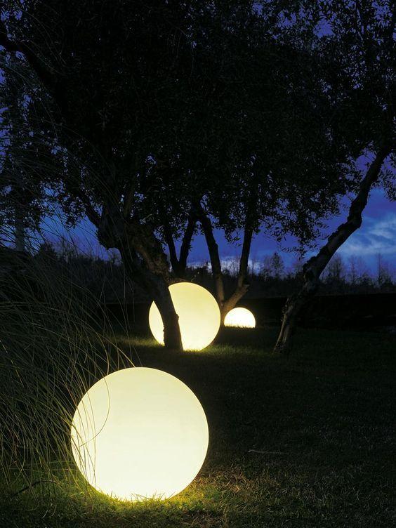 Bolas de LED no meio do gramado com árvores
