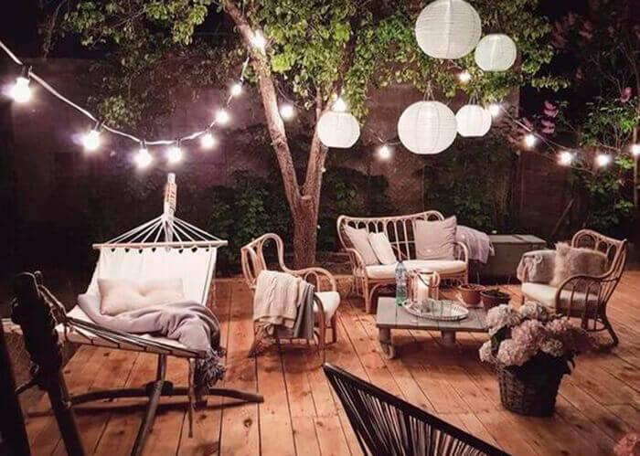 Deck de madeira com várias cadeiras e um balanço com iluminação de cordão de luz_
