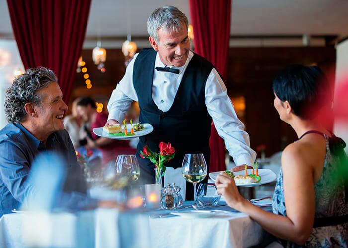 Garçom servindo pratos na mesa de restaurante chique, com um homem e uma mulher