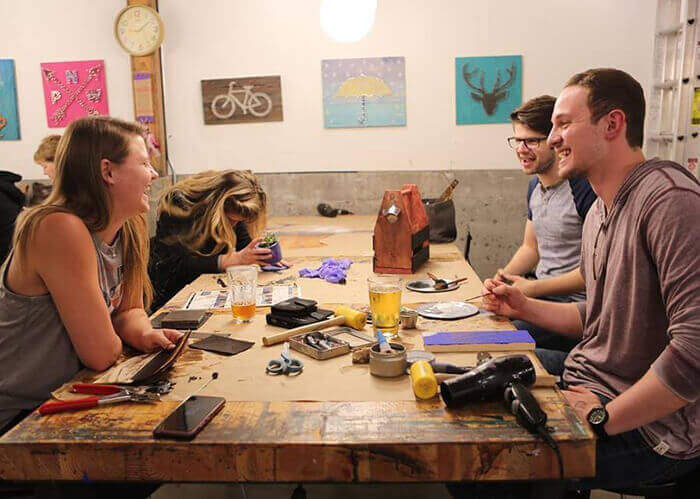 Pessoas sorrindo, sentadas em volta de uma mesa de madeira com várias ferramentas e copos de cerveja