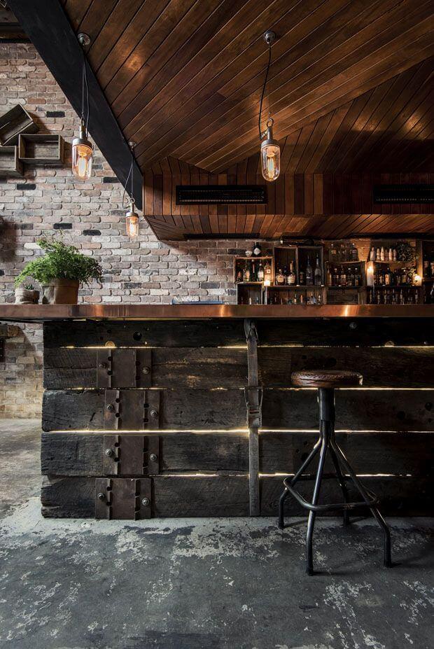 bar com chão de cimento queimado, desgastado. Banqueta alta de ferro, balcão com base de madeira