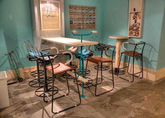 ambiente interno nas cores pasteis e azul com mesas e cadeiras de bicicleta