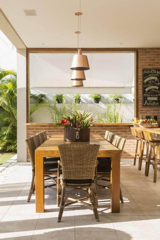 mesa externa de madeira com cadeiras de vime e pendente sobre a mesa.