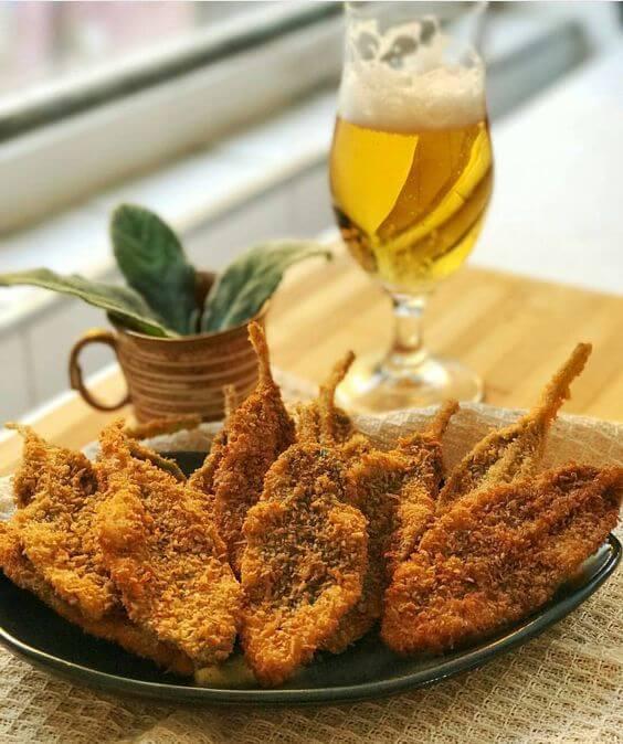 prato da planta peixinho frita, acompanhada com uma taça de cerveja