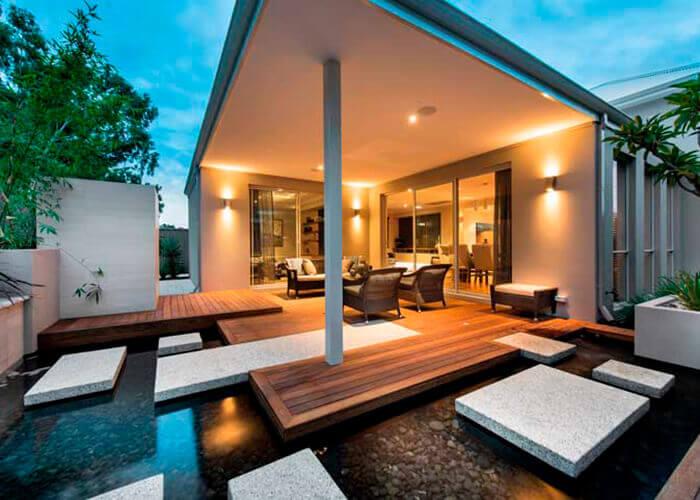varanda de casa aberta com jogo de poltranas e lago artificial na frente.