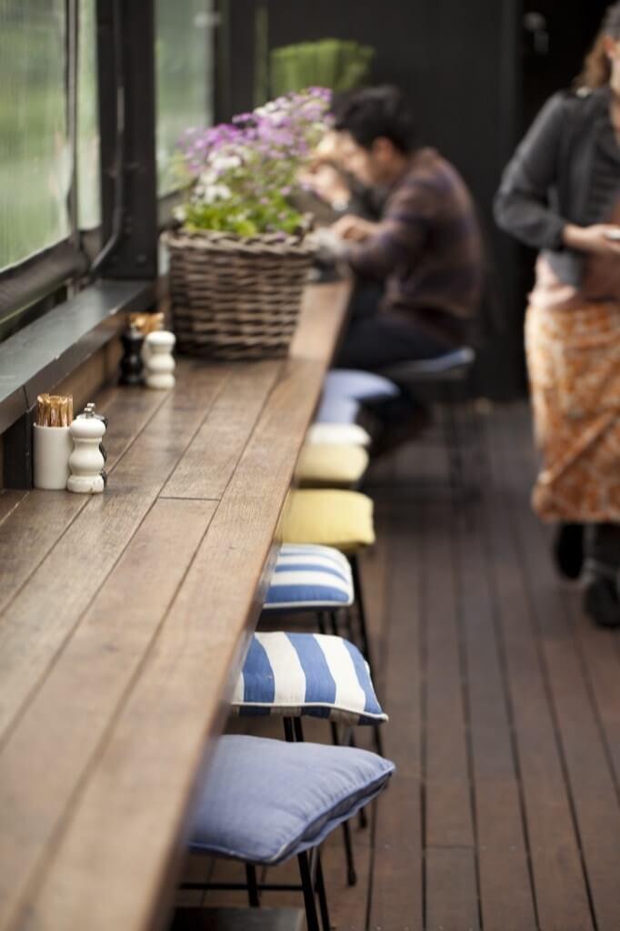 Pessoa desfocada sentada ao fundo de uma bancada de madeira