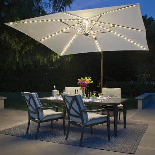 Ambiente externo com mesa e 4 cadeiras e ombrelone iluminado