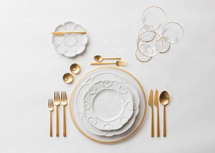 mesa posta vista de cima com pratos detalhados, talheres dourados e taças.