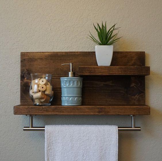 pequena prateleira de madeira bruta com espaço para toalha. Decorada com vaso de leguminosa e porta sabonete