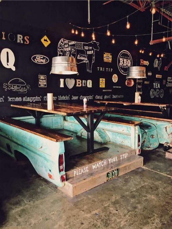 foto de restaurante interno feito com produtos reutilizados como carcaça de carro para dar base a mesa e bancos.
