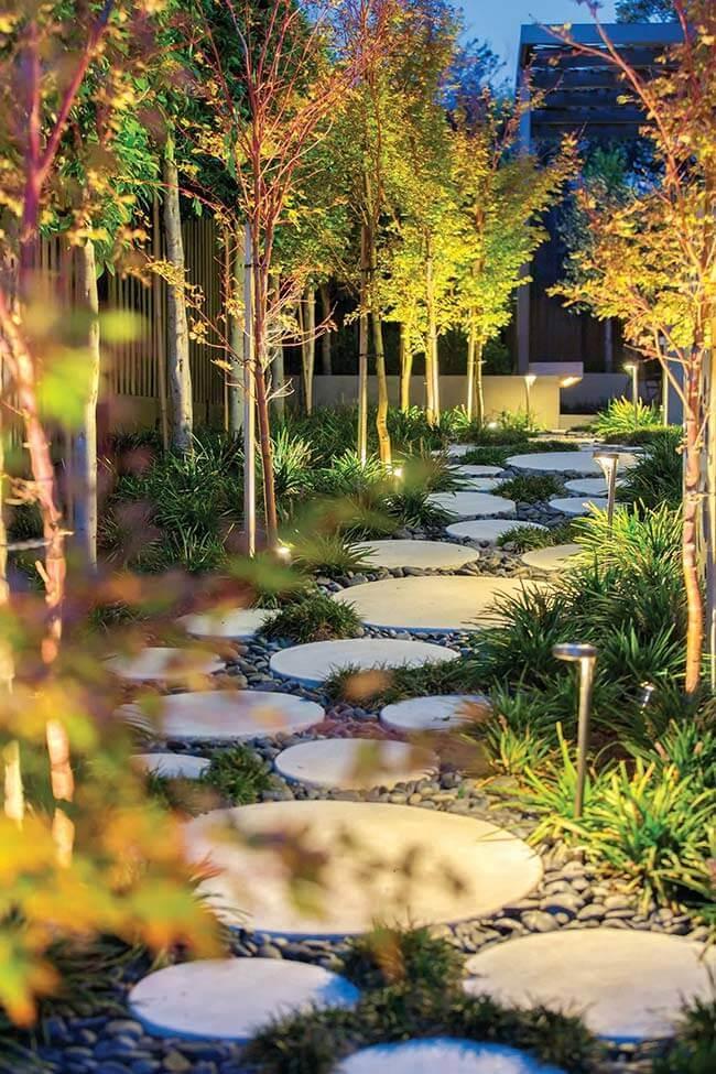 jardim com iluminação externa fazendo caminho de pedras iluminados com balizadores
