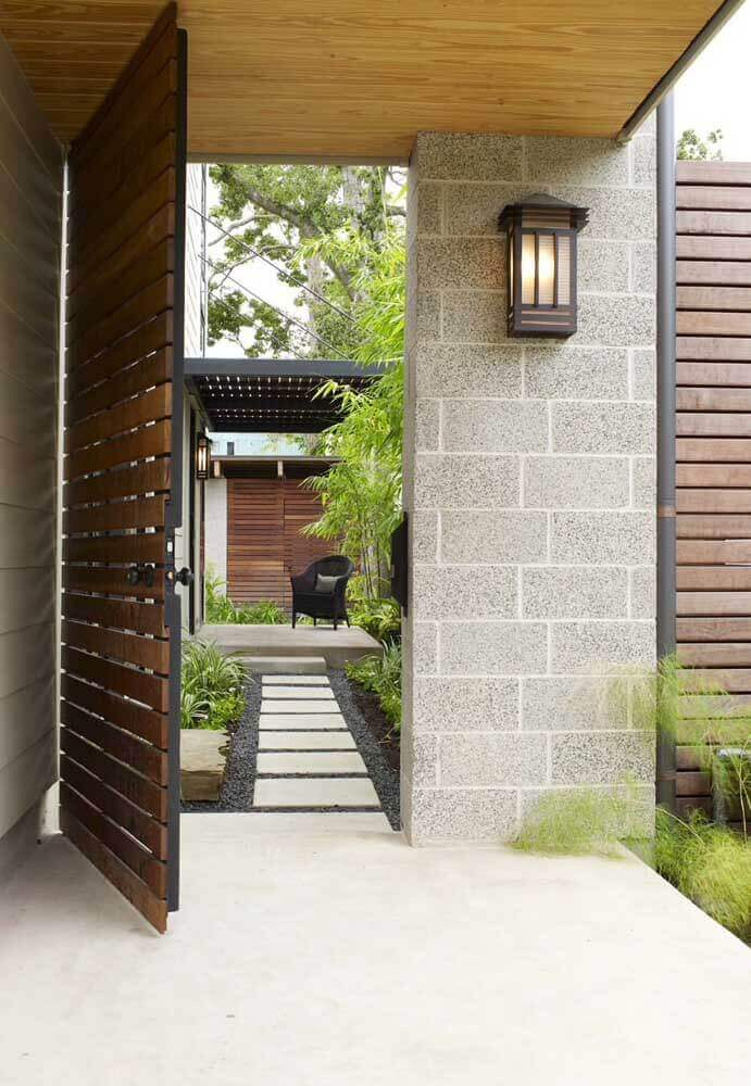 fachada de casa com porta grande de madeira aberta com parede de blocos de cimento