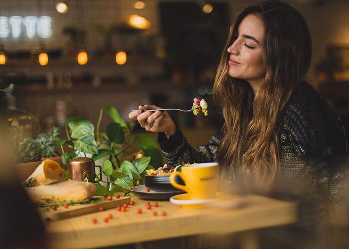 Mulher em um restaurante comendo macarrão com um semblante tranquilo e sensação de satisfação