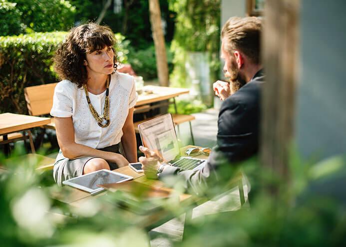 Uma mulher e um homem conversando sobre trabalho em um ambiente aberto com folhag