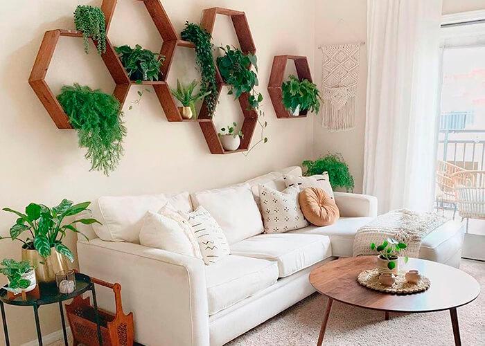 sala de estar com sofá branco, mesinha lateral de ferro, mesinha de centro em madeira.Ornamentação na parede com nichos em favo de m