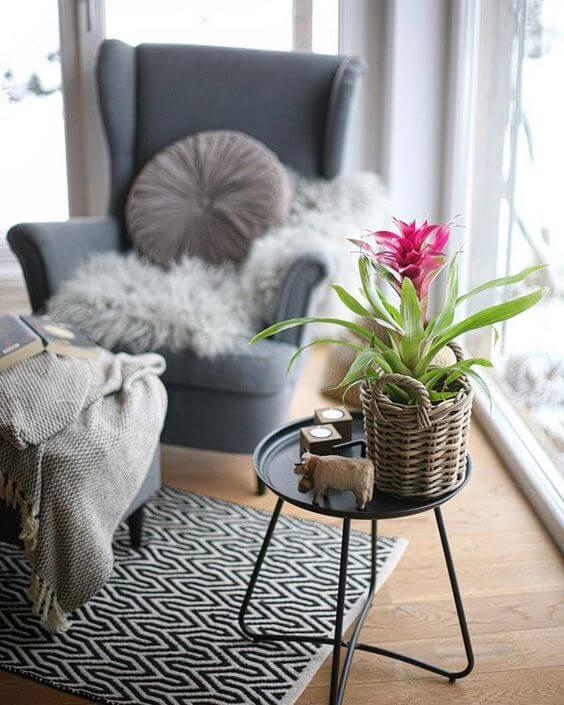 Em foco flor bromélia em cima da mesinha lateral ao fundo sofá cinza