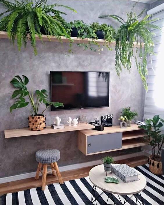 sala de tv com parede cinza e prateleiras de madeira com várias flores