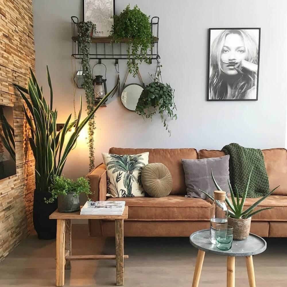 Sala de estar com sofá marrom, mesinha de centro lateral de madeira e quadros, espelho e plantas para ornamentar
