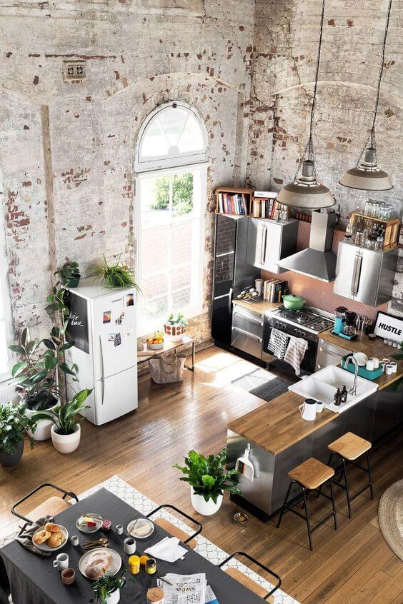 Cozinha com parede rústica chão de madeira. Com elementos de madeira e ferro.