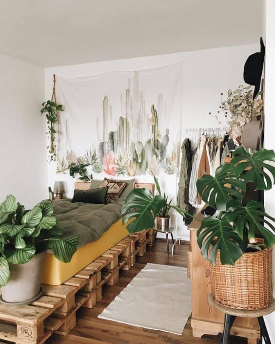 Quarto com cama feita de palete e muitas flores