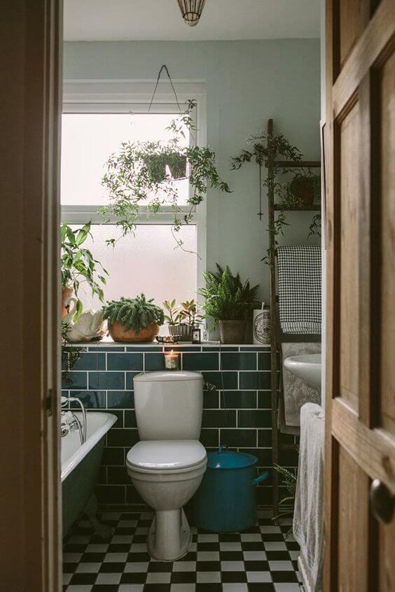 banheiro com piso quadriculado e ornamentado com plantas