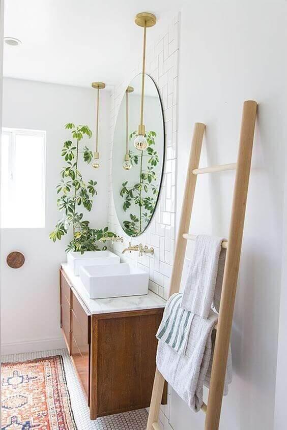 Pia do banheiro com duas cubas brancas e espelho redondo. Pendentes e Planta.