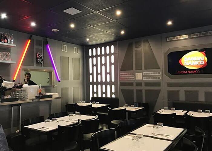 Ambiente temático Star Wars, mesas brancas, cadeiras pretas, parede com textura e decorada com sabre de luz vermelha e roxa