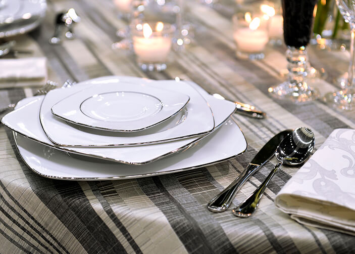 mesa restaurante com toalha listrada em tons de cinza pratos brancos em cima