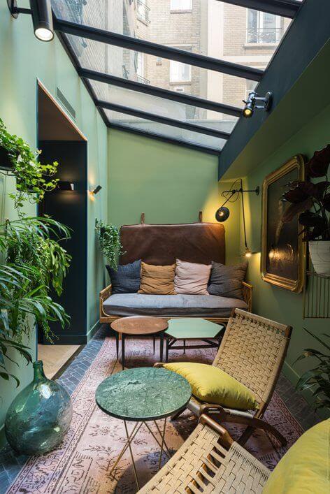 Varanda com paredes verdes, teto transparante e folhagens
