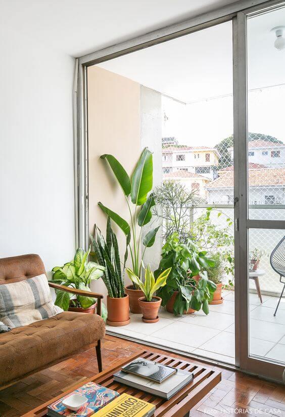 Sofá marrom de frente a porta da sacada com várias plantas
