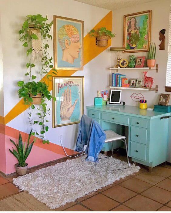 Cantinho da casa com faixas coloridas pintadas na parede e flores penduradas e escrivaninha azul antigo