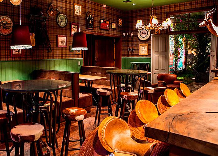 Bar decorado com balcão rústico de madeira, banquetas de sela de cavalo, parede metade de madeira verde, e outra com papel de parede xadrez com vários quadros