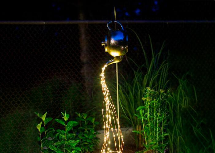 Chaleira derramando luzinhas, usada como decoração na iluminação externa