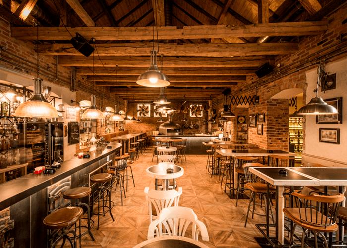 Foto de bar interno com chão de piso que remete tacos de madeiras, banquetas e cadeiras de madeira e ferro.