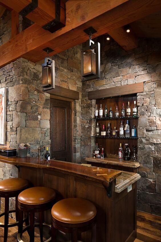 banquetas altas com estofado em couro, próximo ao balcão de madeira. Parede de pedras com prateleiras apoiando bebidas
