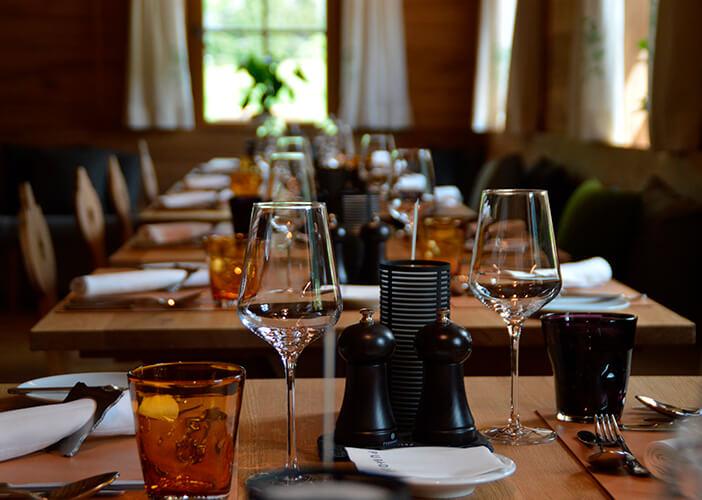 mesas de restaurantes arrumadas com taças, copos, pratos e talheres