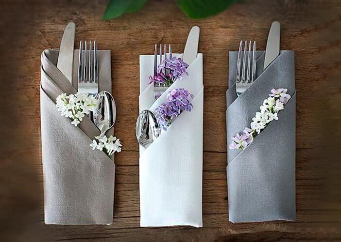 3 guardanapos de tecido dobrados com talheres dentro, ornamentado de flores, em fundo amadeirado.