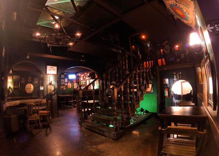 Bar interno com detalhes em madeira, pouca luz, escada central