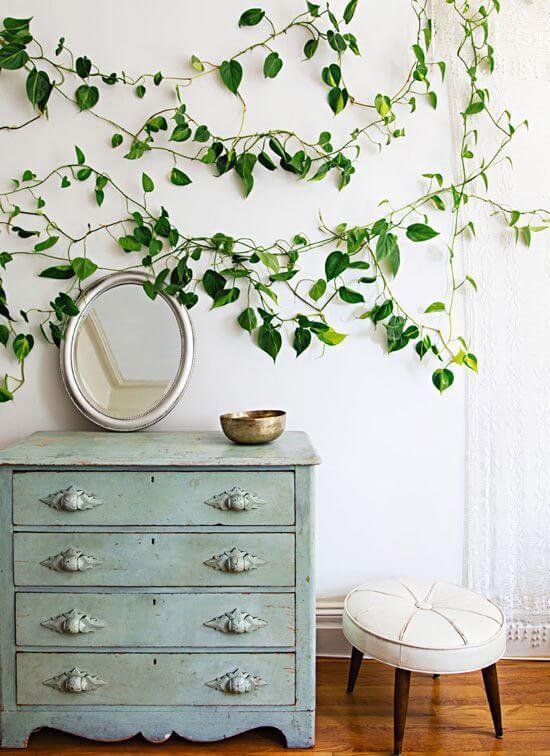 Comoda azul turquesa envelhecida segurando espelho oval e acima na parede planta jiboia
