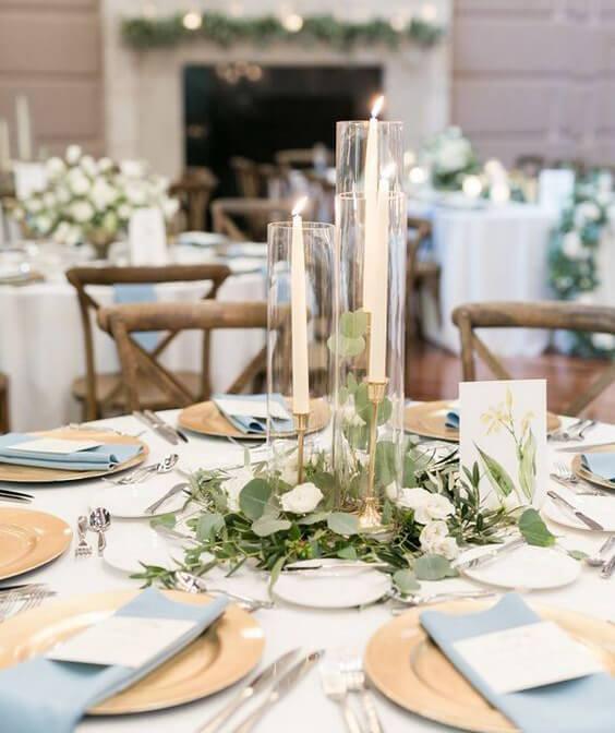 mesa redonda com toalha clara, pratos amarelos e guardanapo azul claro, com arranjo central com velas