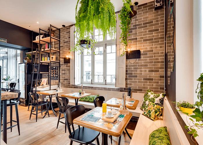 ambiente interno da cafeteria com mesas personalizadas, parede de tijolinho e booth com almofadas