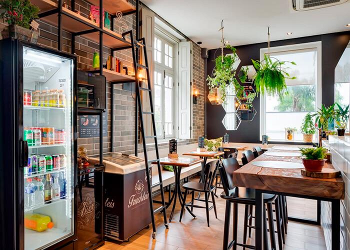 ambiente interno de cafetería com plantas para decoração, parede de tijolinhos, mesas de madeira.