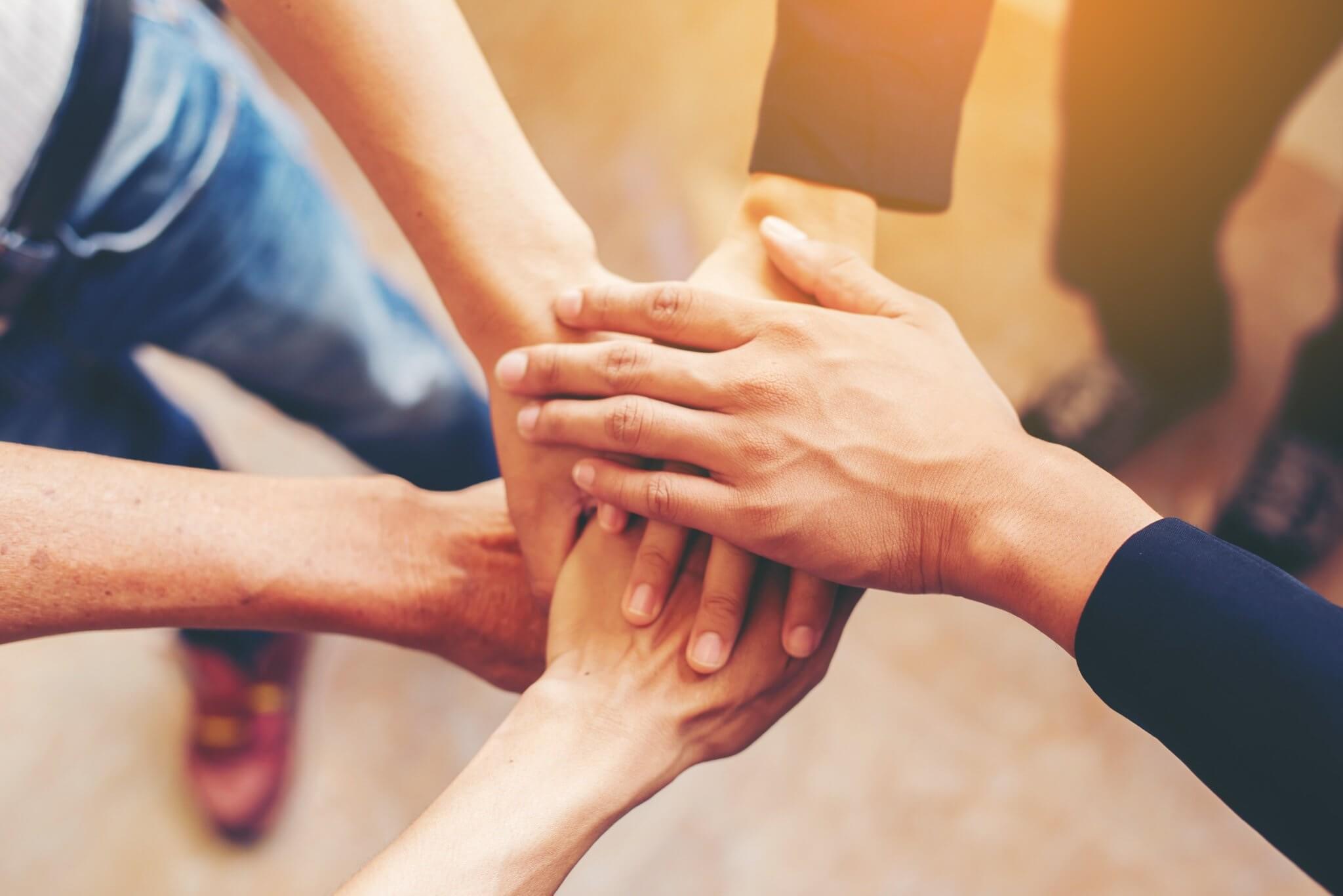 Mãos uma em cima da outra em gesto de estão todos juntos como uma equipe