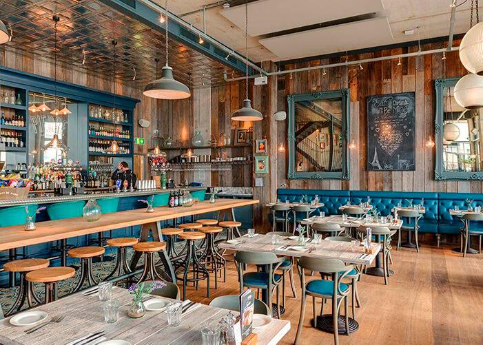 ambiente com chão e paredes de madeira. detalhes nas molduras e cadeiras com azul turquesa