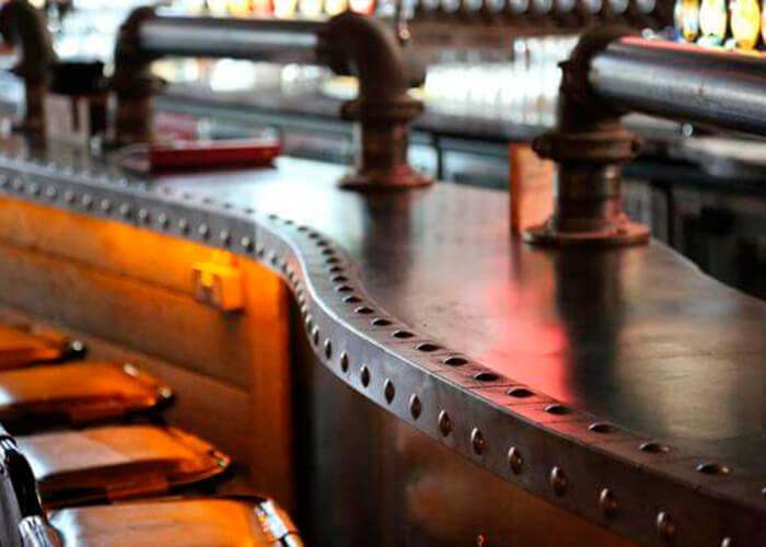 foto detalhe de um balcão de bar de madeira revestido em suas bordas com metal_