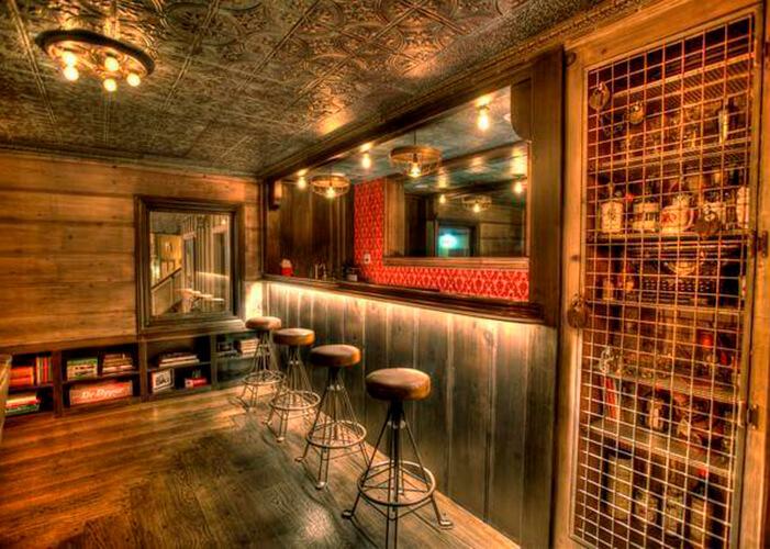 Bar com chão, paredes e balcão em madeira, banquetas de metal com estofado em couro