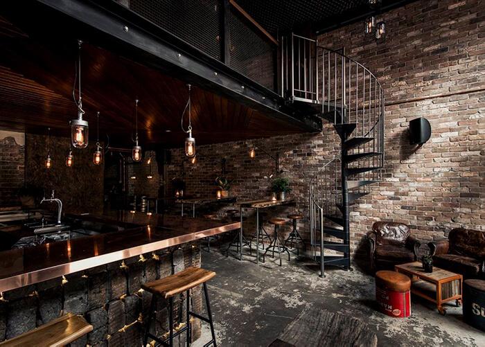 Bar com piso de cimento queimado descascado. Banquetas de madeira com pés de metal_