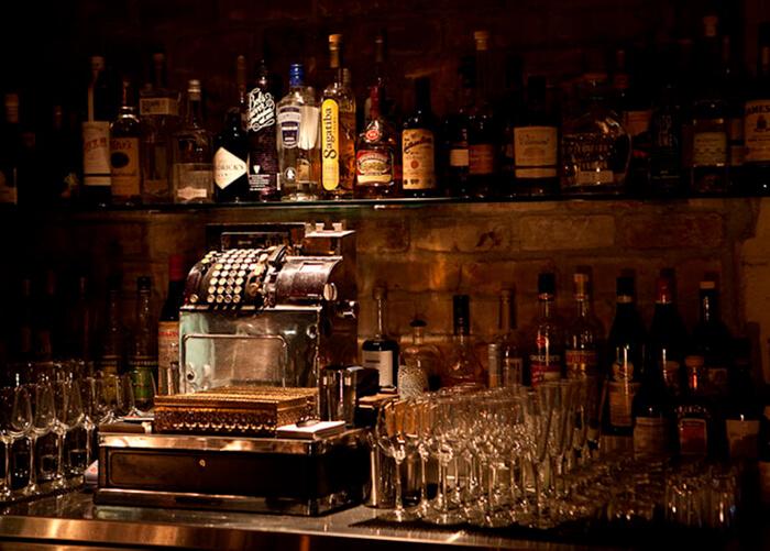caixa registradora antiga de metal, dos lados copos e taças e acima prateleira de vidro com várias bebidas_