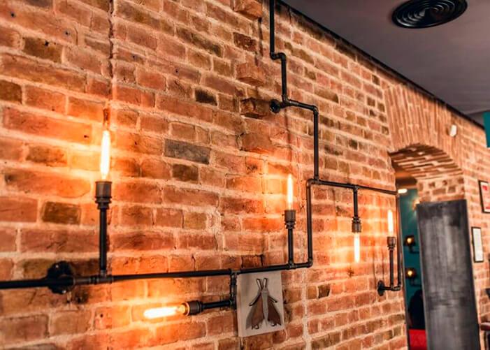 Reaproveitamento de canos como luminárias expostos na parede de tijolos aparente